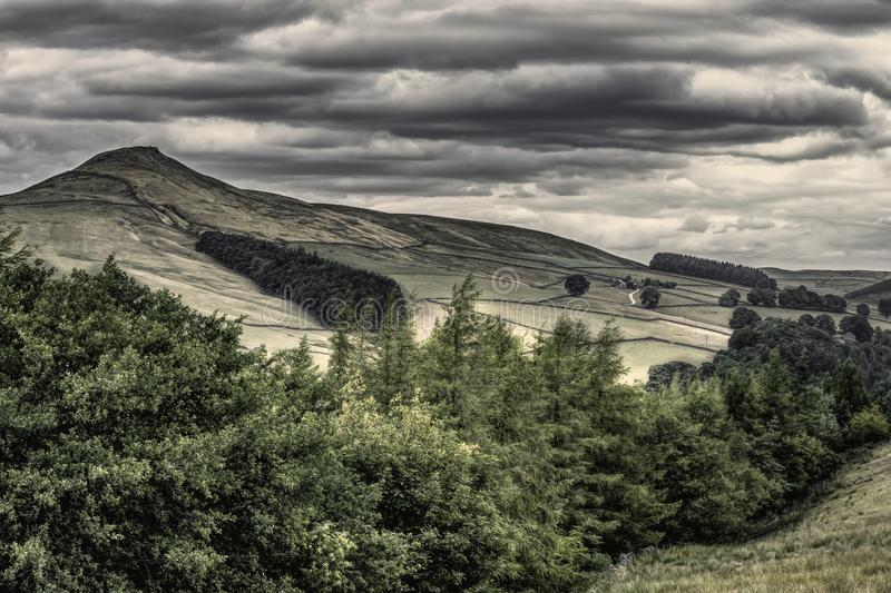 Idyllic landscape of Peak District National Park, Derbyshire, Uk. Scenic view on mountain valley with trees in foreground and summit in background.Dramatic sky royalty free stock photography