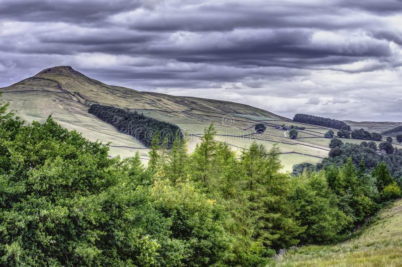 Idyllic landscape of Peak District National Park, Derbyshire, Uk. Scenic view on mountain valley with trees in foreground and summit in background.Dramatic sky stock photos