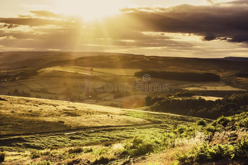 Idyllic landscape of Peak District National Park, Derbyshire, Uk. Sunset over scenic mountain valley.Sun shining trough dark clouds during golden hour.Beautiful stock photos