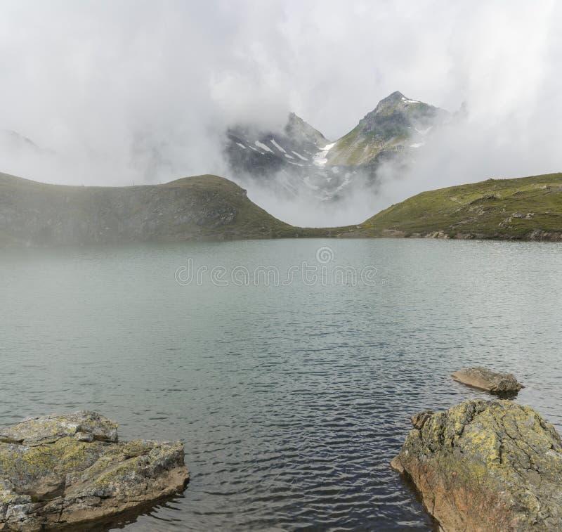 Idyllic mountain lake with fog lifting to reveal high alpine mountains stock image