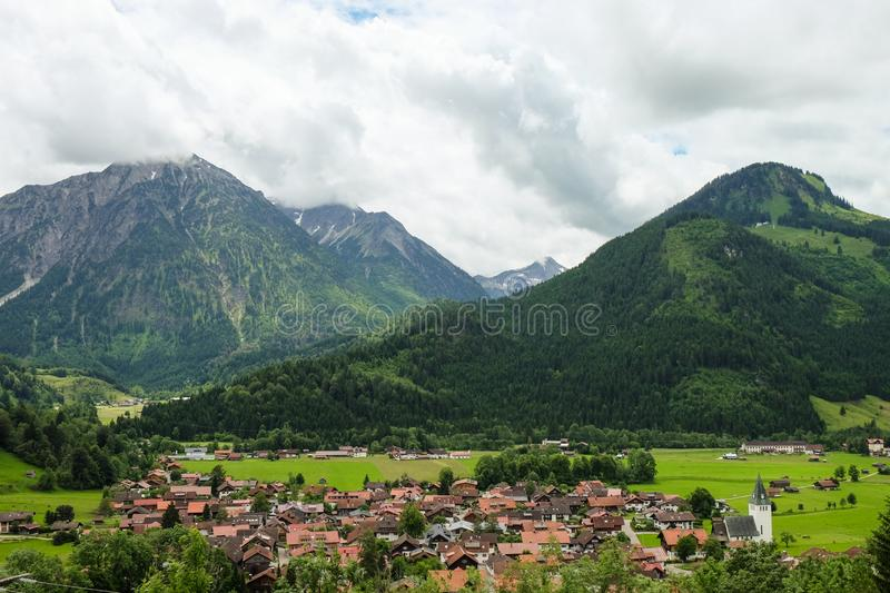Idyllic mountain landscape with a small village and mountains in the background royalty free stock image