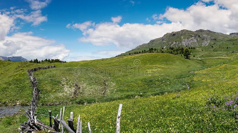 Idyllic mountain landscape in the summertime with a traditional wooden fence in the foreground. An idyllic mountain landscape in the summertime with a stock image