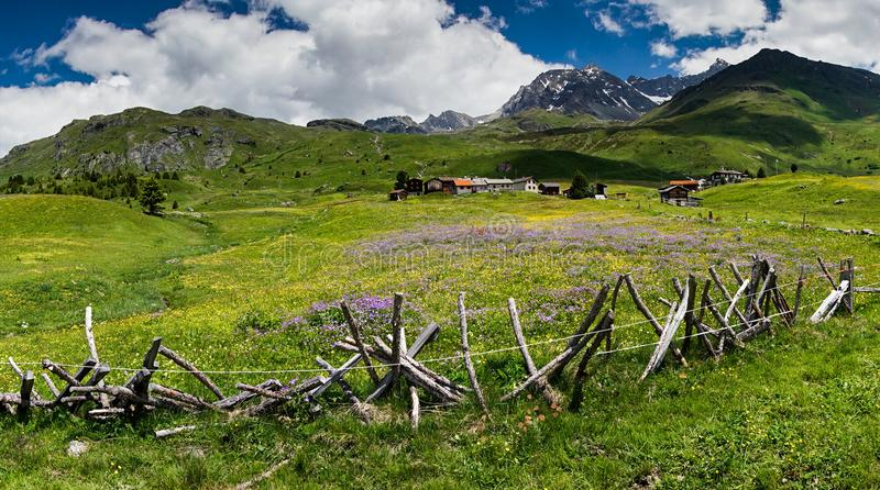 Idyllic mountain landscape in the summertime with a traditional wooden fence in the foreground. An idyllic mountain landscape in the summertime with a royalty free stock image