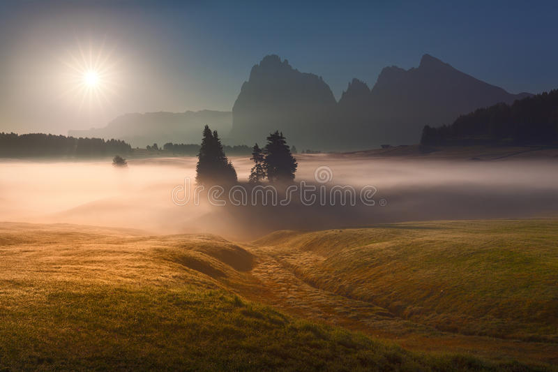 Idyllic mountain scenery against the sunlight. Misty landscape view in Alpe di Siusi or Seiser Alm towards the rising sun. Beautiful photo in back lighting stock photos