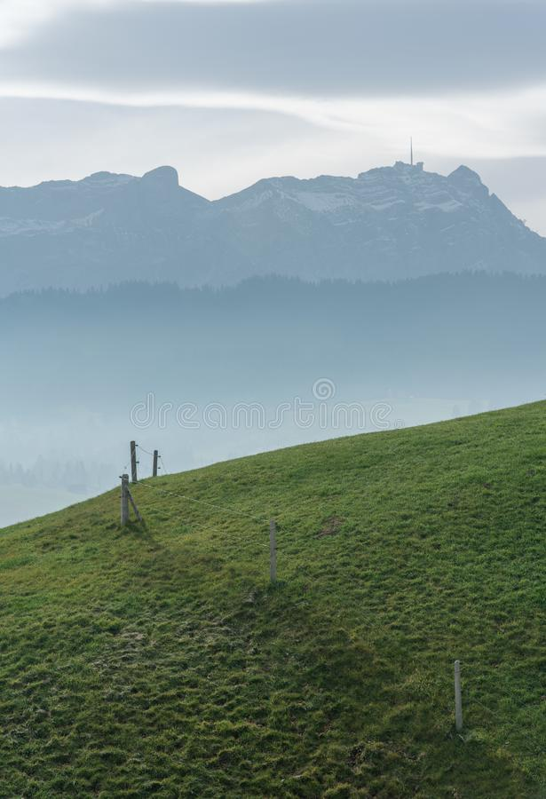 Idyllic and peaceful mountain landscape with a wooden fence on a grassy hillside and a great view of the Swiss Alps behind royalty free stock images