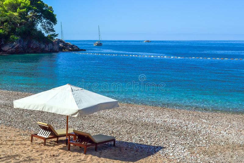 Idyllic scene of deck chairs under an umbrella on a clean beach in the hot afternoon sun. stock photo