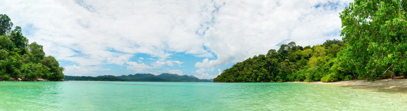 Idyllic tropical clear sea and green island panorama. With calm turquoise water and cloudy sky royalty free stock photography