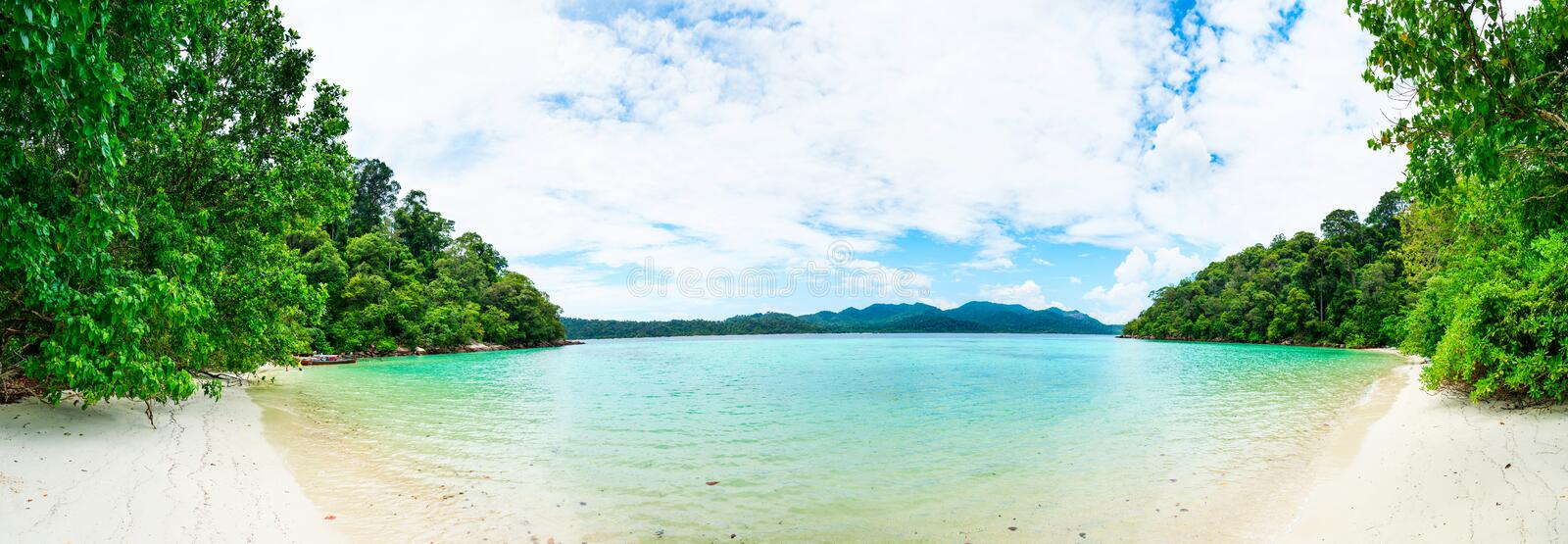 Idyllic tropical clear sea and green island panorama. With sand beach and calm turquoise water royalty free stock images