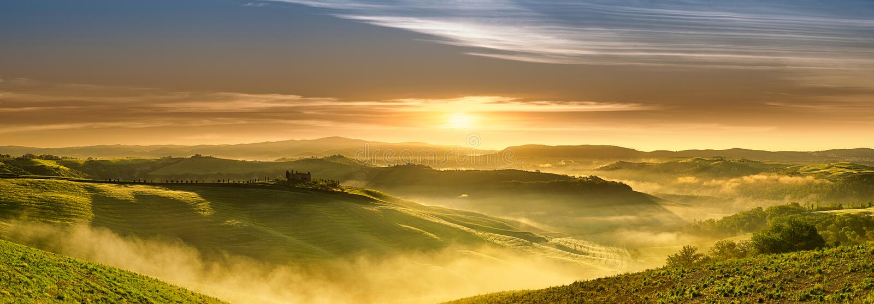 Idyllic view, foggy Tuscan hills in light of the rising sun. Panorama, Italian beautiful landscape, foggy rolling fields of Tuscany in light of the rising sun royalty free stock photo