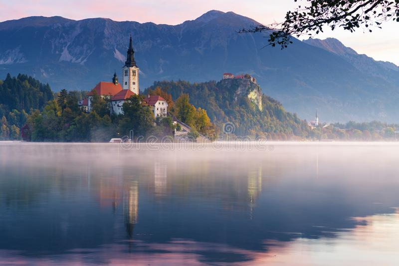 Lake Bled at sunrise. Church on island with castle and mountains in background. Idyllic view of lake Bled during sunrise in the autumn. Mist lingering over the royalty free stock photos