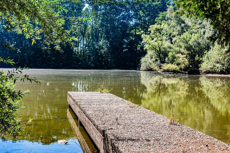 Idyllic view of a lake surrounded by trees seen from a small wooden pier stock images