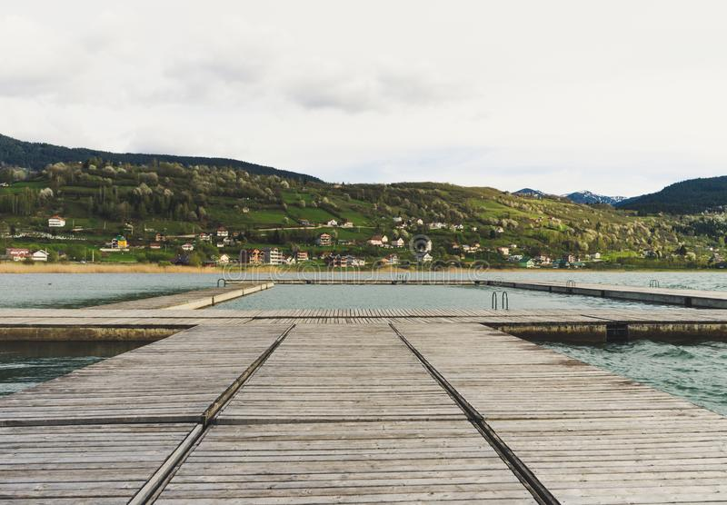 Idyllic view of the wooden pier in the lake with mountain scenery background. Plav lake montenegro royalty free stock photos