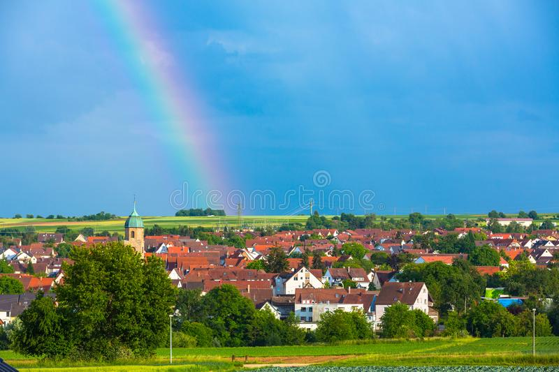 Idyllic village with rainbow and blue sky. Idyllic view to a village with rainbow and blue sky stock photos