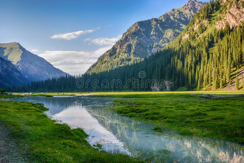 Idylliczny lato krajobraz z wycieczkować ślad w górach z pięknymi świeżymi zielonymi halnymi paśnikami, rzeka z odbiciem obraz stock