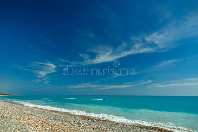 Idyllisch steenstrand met waterstraal en blauwe hemel royalty-vrije stock fotografie