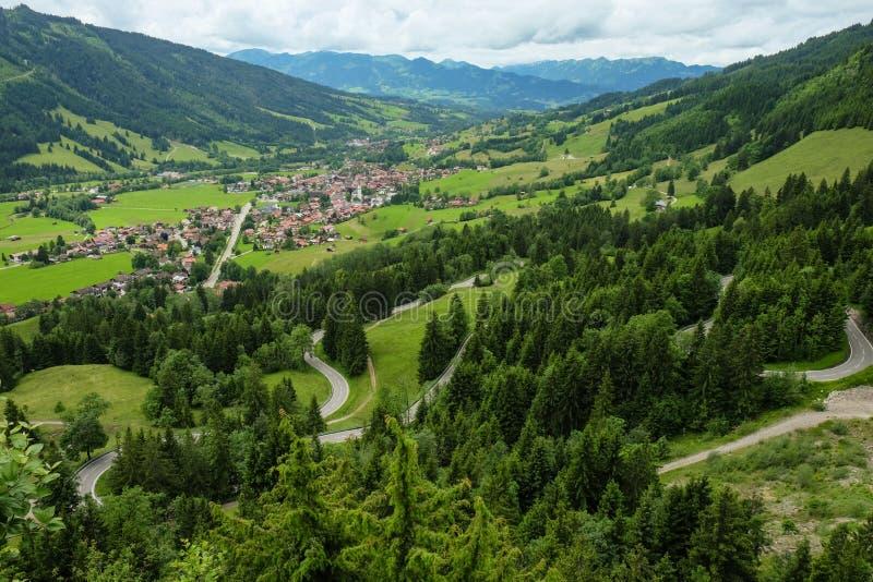 Idyllische Berglandschaft mit einem kleinen Dorf und Berge im Hintergrund lizenzfreie stockfotos
