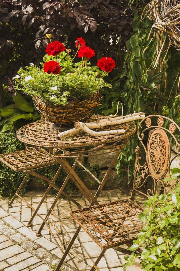 Idyllische Sitzecke im Garten mit Blumenanordnung und t lizenzfreie stockfotos