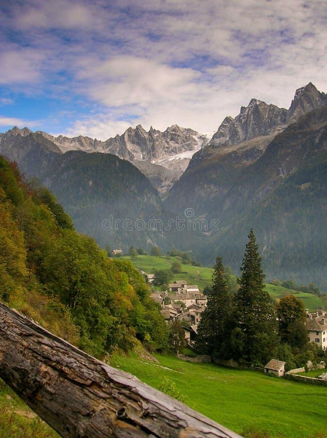 Idyllisches und malerisches Bergdorf in den Alpen von der Schweiz mit einer großen Berglandschaftsansicht hinten stockfotos