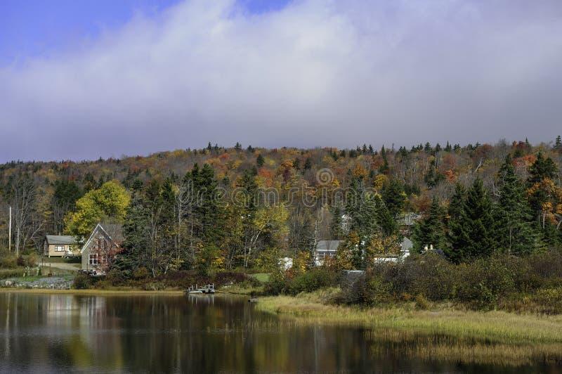 Idyllisk lakesideuppehälle under nedgånglövverk i New England royaltyfria foton