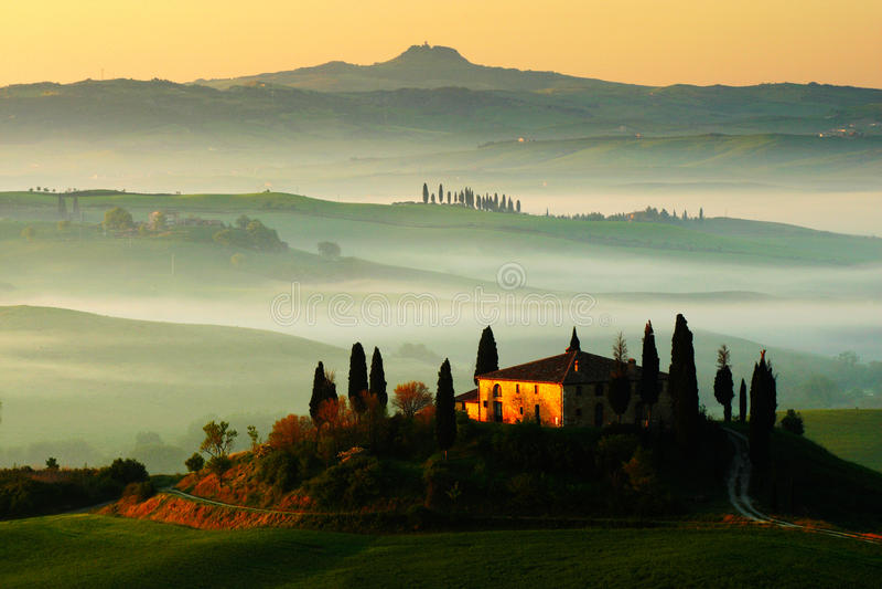 Idyllisk sikt av bergig jordbruksmark i Tuscany i härligt morgonljus, Italien Dimmigt landskap i Tuscany Belvedere i Tuscanyen arkivfoton