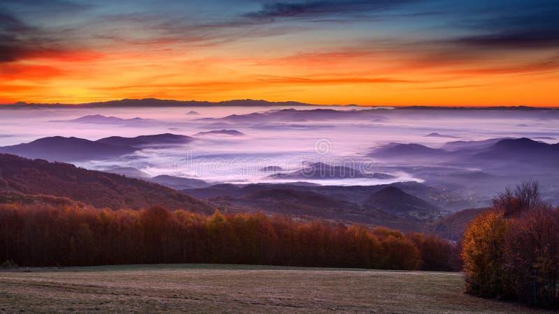 Idylliskt berglandskap på dimmig gryning royaltyfria bilder