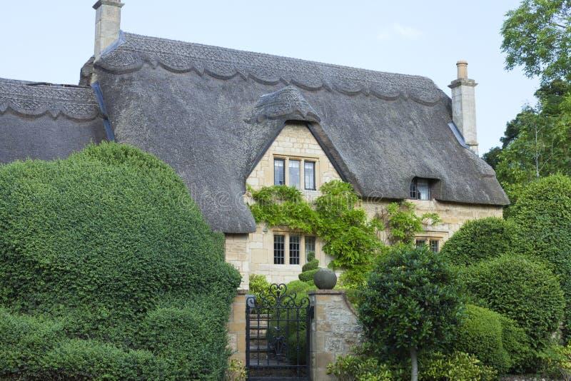 Idylliskt gammalt engelskt hus med topiaryträdträdgården fotografering för bildbyråer