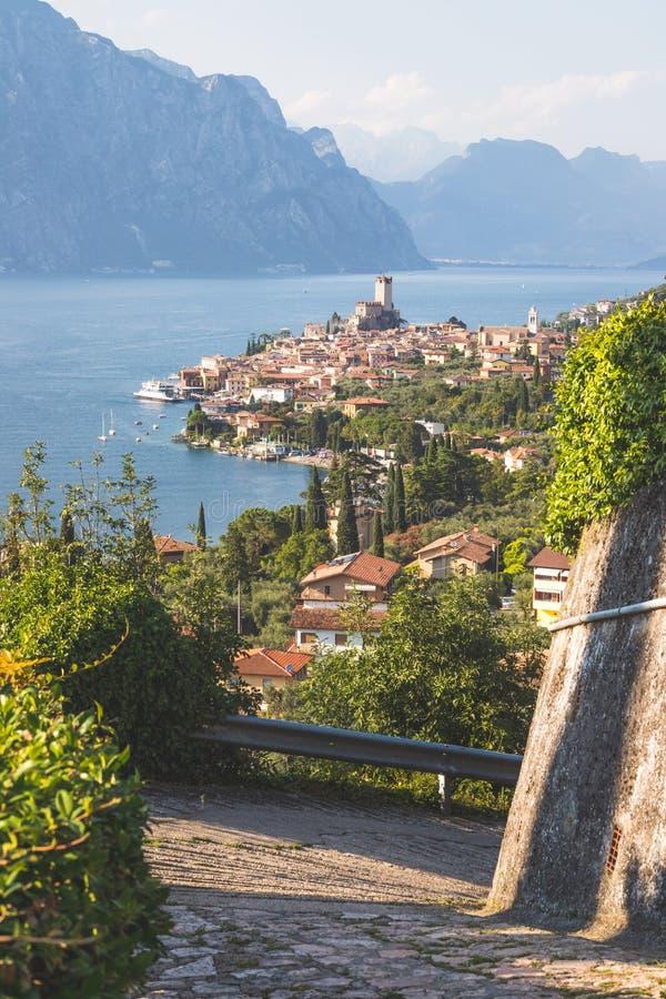 Idylliskt kustlinjelandskap i Italien: Bl?tt vatten och en gullig by p? lago di garda, Malcesine royaltyfri foto