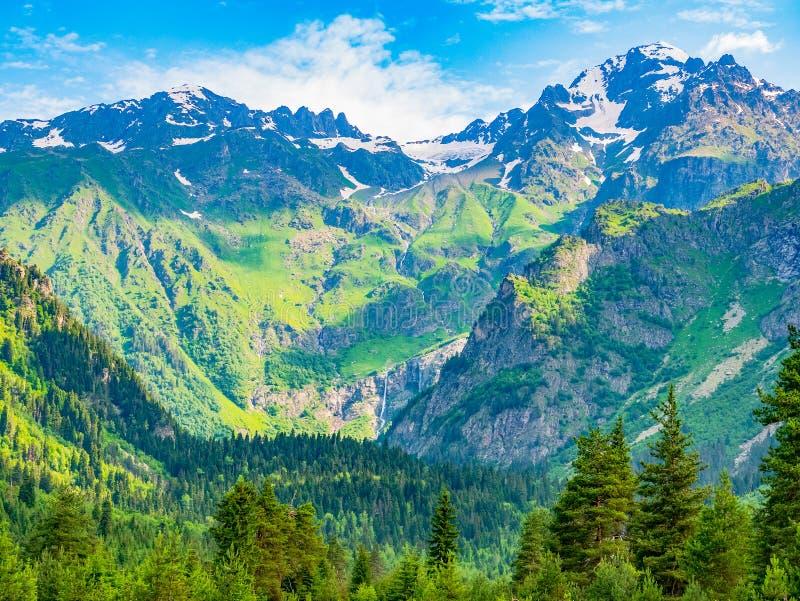 Idylliskt landskap med blå himmel, den gröna skogen och den snowcapped bergöverkanten Svanetia region, Georgia arkivbild
