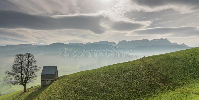 Idylliskt och fridsamt berglandskap med en avskild träladugård och ett ensamt träd på en gräs- backe och en stor sikt av Swien arkivbilder
