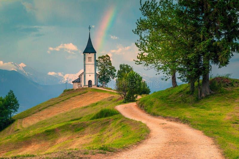 Idylliskt regnbågelandskap med den helgonPrimoz kyrkan, nära Jamnik, Slovenien royaltyfri foto