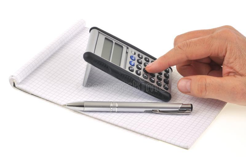 Iemand die een calculator op een blocnote op een witte achtergrond gebruiken royalty-vrije stock foto's