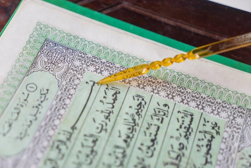 Iemand leest heilige Quran met wijzerstok stock foto's