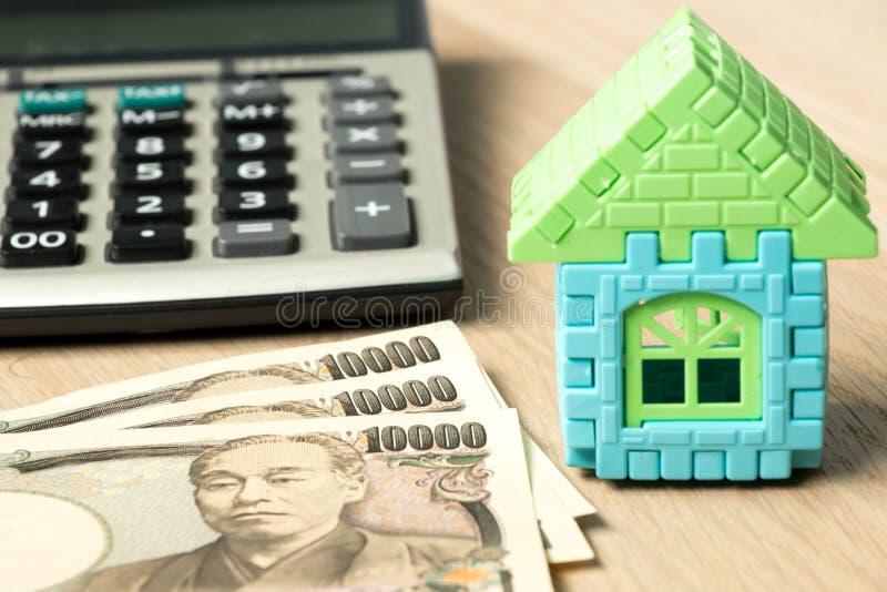 Iene japonês com modelo da casa e calculadora no fundo de madeira foto de stock royalty free