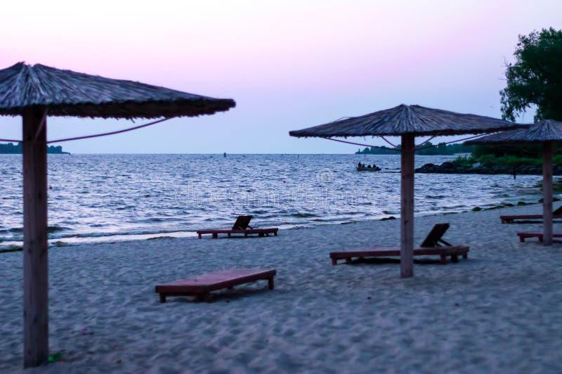 Iew av den sandiga stranden med bambuparaplyer och solsängar på soluppgång arkivfoton