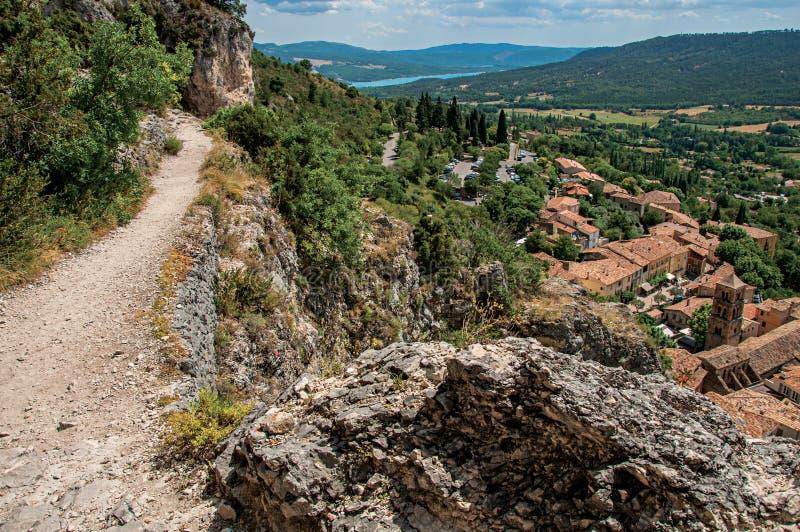 Iew do trajeto de pedra acima dos telhados e da torre de sino em Moustiers-Sainte-Marie imagens de stock