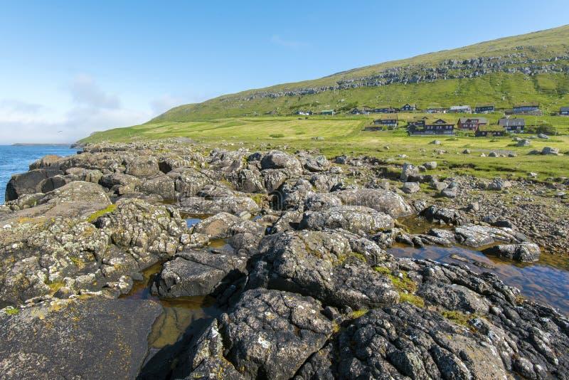 Iew på Kirkjubour byhus från den steniga havkostnaden fotografering för bildbyråer