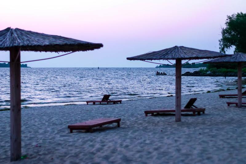 Iew piaskowata plaża z bambusowymi parasolami i słońc łóżkami przy wschód słońca zdjęcia stock