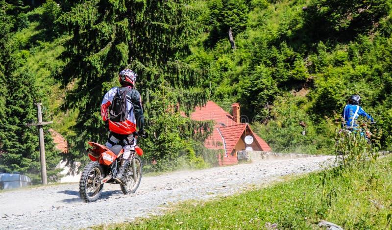 Iezerbergen - Roemenië - 2019 Jonge fietser die een rit in het bos van Iezer-Bergen op een dwarsmotor hebben stock foto