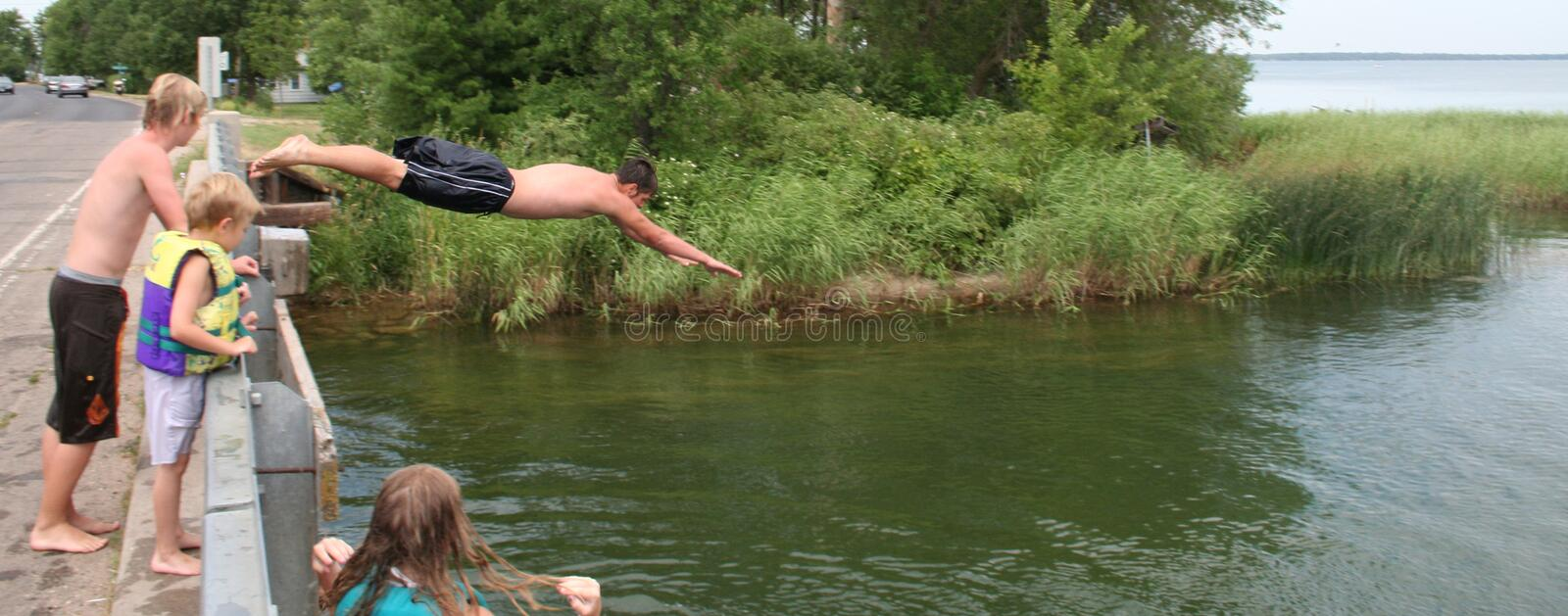 If all your friends jumped off a bridge... Action shot of a bridge diver. Teenage boy mid-dive off of a bridge into a river with three other kids watching stock image