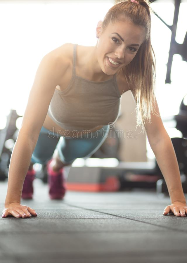 If it burns, you `re doing it right. Sportswoman working push-ups at gym. Close up stock image