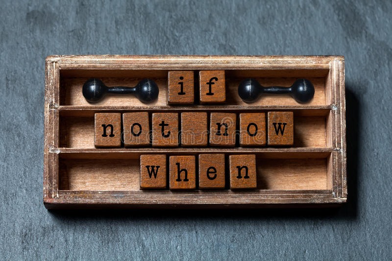 If not now when. Motivation and success future management quote. Vintage box, wooden cubes with old style letters. Ancient dumbbells. Gray stone textured stock images