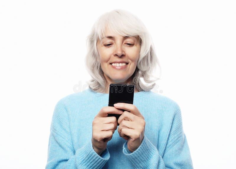 Ifestyle, familj- och folkbegrepp: den gamla farmodern talar till hennes barnbarn vid telefonen, ler och hälsar dem arkivbilder