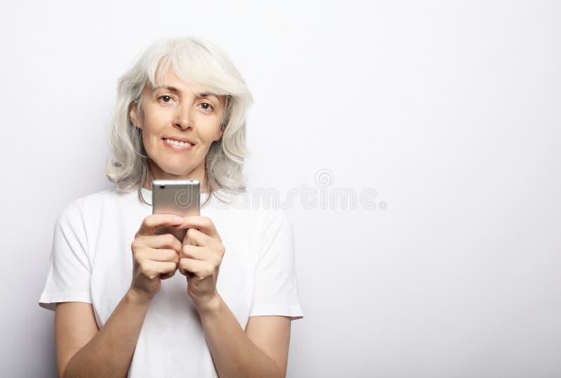 Ifestyle, familj- och folkbegrepp: den gamla farmodern talar till hennes barnbarn vid telefonen, ler och h?lsar dem royaltyfria bilder