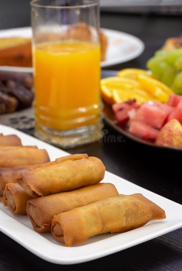 Iftar bufeta stół Wiosny rolka, świeży sok pomarańczowy, samosa przekąska, wiosny rolka i owoc tła pojęcie, iftar Ramadan zdjęcie stock