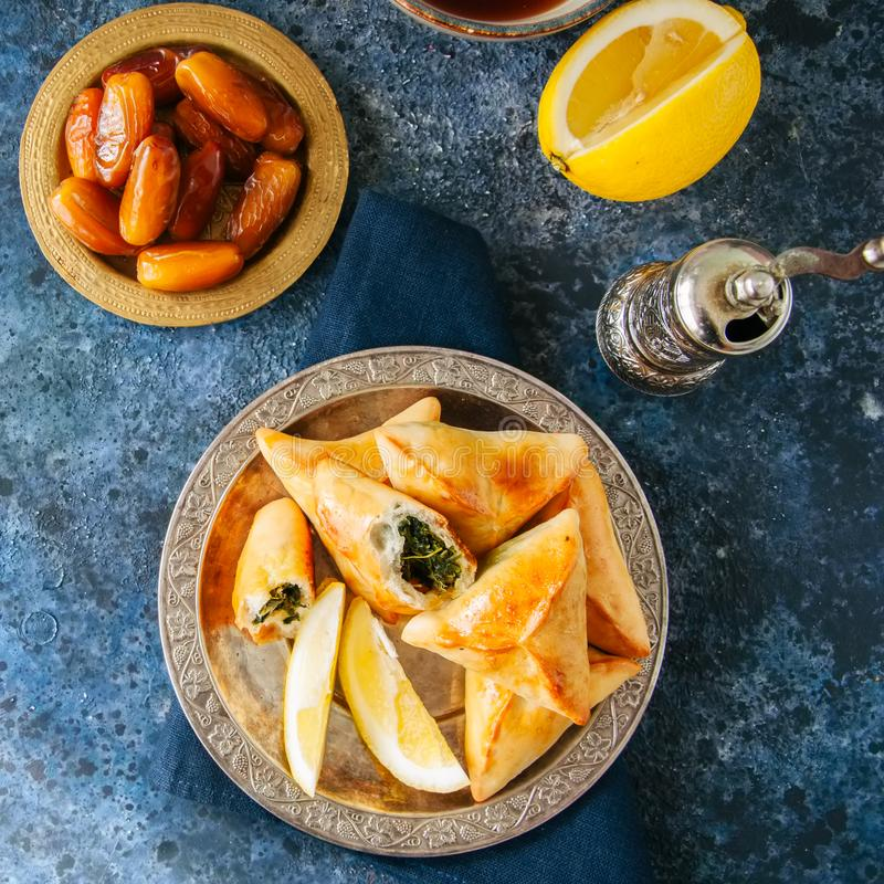 Iftar food during ramadan, arabic and middle eastern food concept. Fatayer sabanekh - traditional arabic spinach triangle hand pi stock image