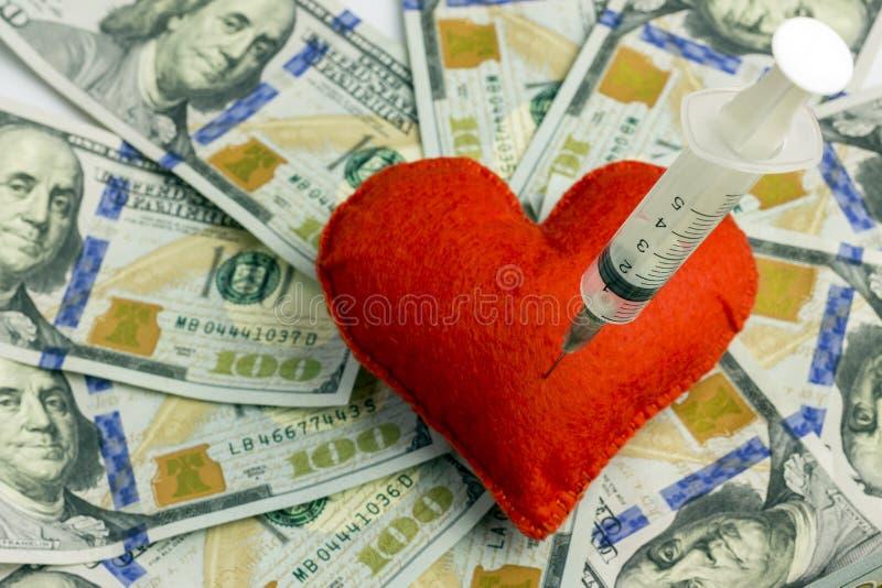 Igła medyczna strzykawka wtyka w czerwonym sercu przeciw tłu dolarów amerykańskich rachunki Pojęcie zaraźliwa miłość, fotografia royalty free