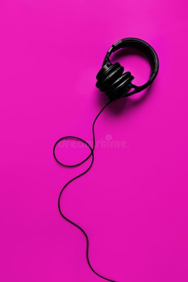 Ig hörlurar på en purpurfärgad bakgrund arkivbild