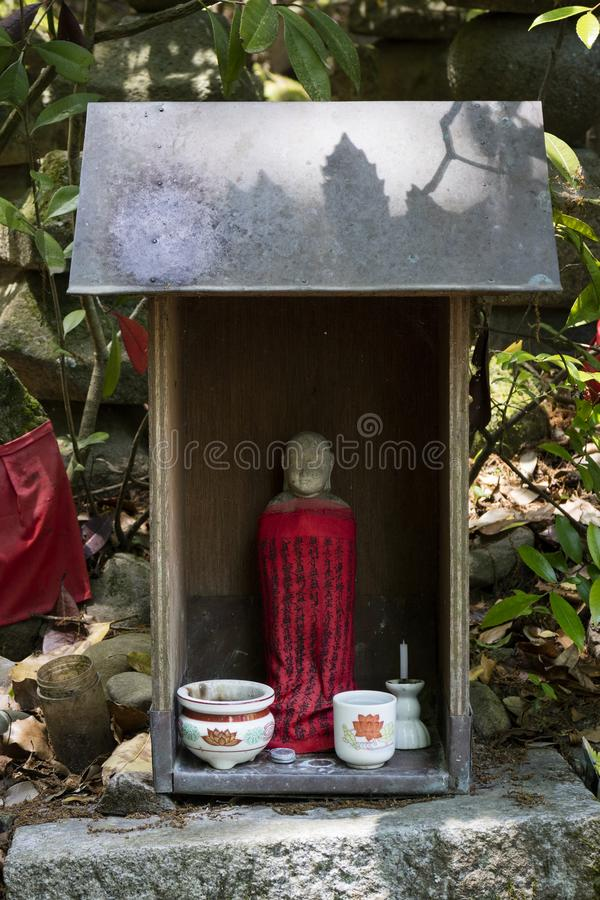 Iga Ueno - Japan, June 1, 2017: Traditional stone carved Jizo wi. Th red skirt honored and respected with a cup of water and incense in Ueno park stock photo
