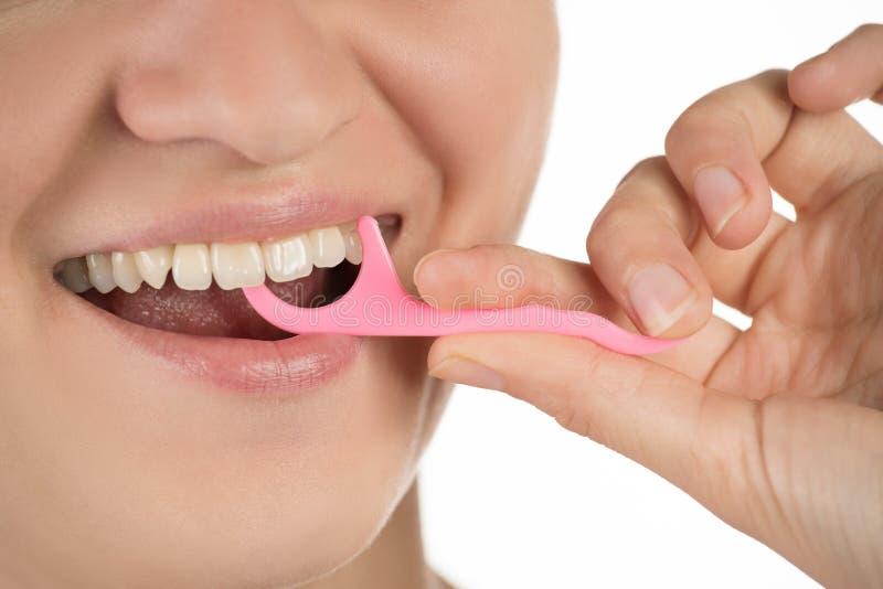 Igiene della cavità orale La ragazza pulisce i denti con filo di seta, immagini stock