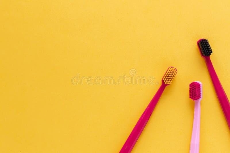 Igiene dentale - disposizione piana degli spazzolini da denti, vista superiore, spazio della copia, fondo rosa fotografia stock
